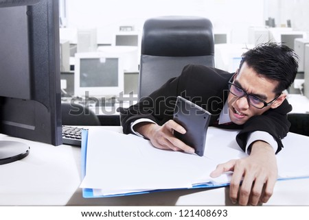 A businessman is holding a calculator worrying about paying bills and making profit - stock photo