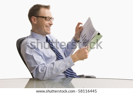 A businessman is seated at a desk and is looking at paperwork with a happy expression on his face.  Horizontal shot.  Isolated on white. - stock photo