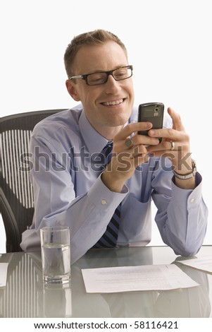 A businessman is seated at a desk in an office and is texting on a cell phone.  Vertical shot.  Isolated on white. - stock photo