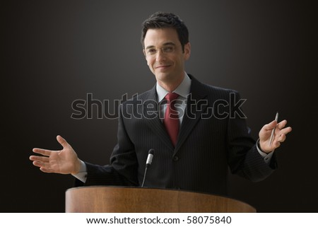 A businessman is standing at a podium with a microphone giving a lecture with outstretched hands. Horizontal shot. - stock photo