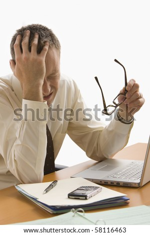 A businessman is stressed out at his work desk.  He has his glasses off and eyes closed.  Vertical shot.  Isolated on white. - stock photo