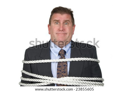 A businessman is tied up by his co-workers - stock photo