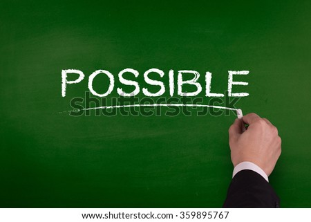 A businessman is writing POSSIBLE concept on blackboard. - stock photo