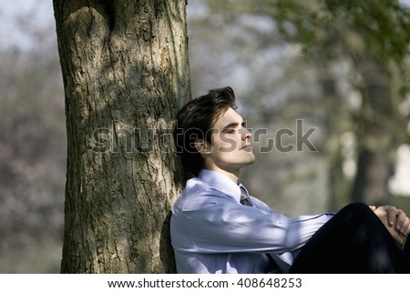 A businessman leaning against a tree, resting - stock photo