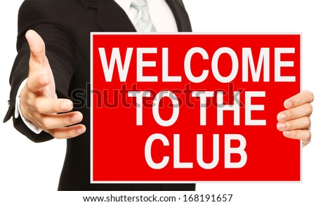 A businessman offering a handshake and holding a welcome sign  - stock photo