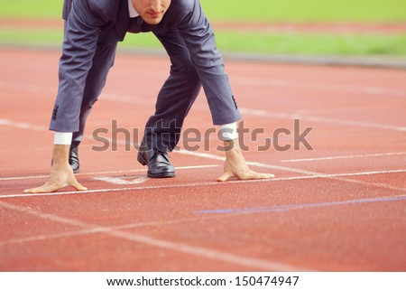 A businessman on a track ready to run  - stock photo