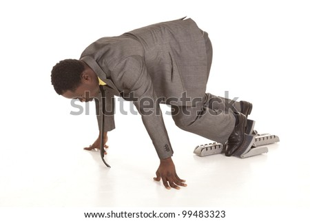 A businessman on racing blocks ready for the business race of work. - stock photo