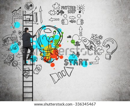 A businessman on the ladder is drawing business management icons and a colourful lightbulb on the concrete wall. The concept of the brainstorm or a start up. - stock photo