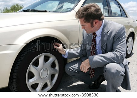 A businessman on the road with a flat tire.  He has just discovered the screw that caused the tire to go flat. - stock photo
