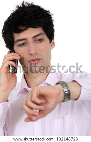 A businessman over the phone looking at his watch. - stock photo