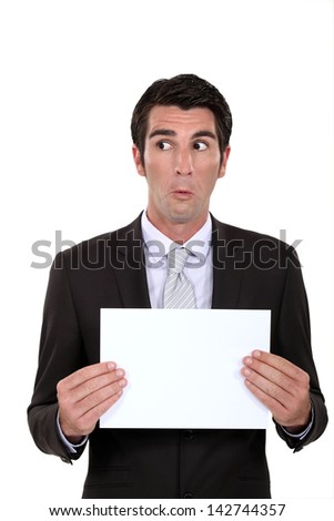 A businessman presenting a poster with a weird facial expression. - stock photo
