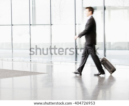 A businessman pulling suitcase along - stock photo