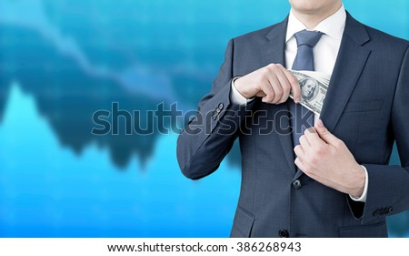 A businessman putting a one-hundred dollar banknote into the chest pocket. Blue graphs at the background. Front view, no head. Concept of getting money. - stock photo