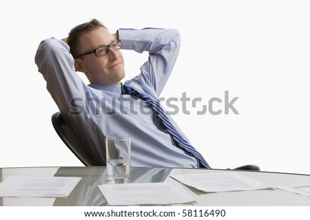 A businessman reclines back in his chair at work with paperwork spread across his table.  Horizontal shot.  Isolated on white. - stock photo