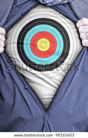 A businessman rips open his shirt and shows how perfect he is for your needs by showing off a target printed on a t-shirt - stock photo
