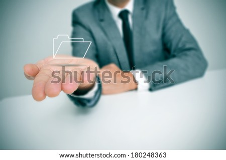 a businessman seating in a desk holding a folder icon in his hand - stock photo