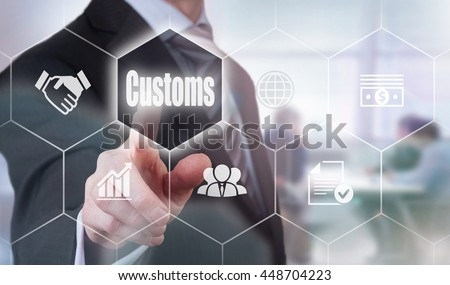 A businessman selecting a Customs Concept button on a clear screen. - stock photo