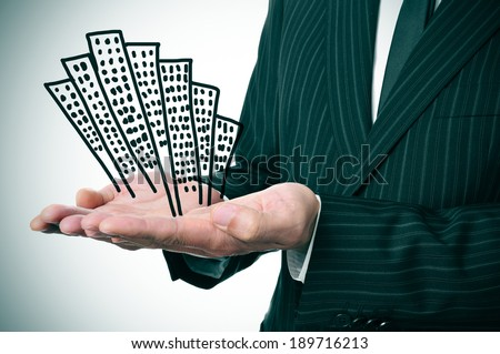 a businessman showing a pile of drawn buildings in his hands - stock photo