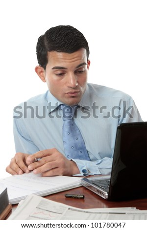 A businessman sitting at desk with paperwork, laptop and notebook working hard. - stock photo