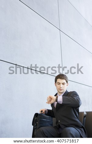 A businessman sitting down looking at his watch holding a briefcase - stock photo