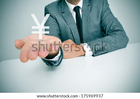 a businessman sitting in a desk showing a chinese yuan or japanese yen sign in his hand - stock photo