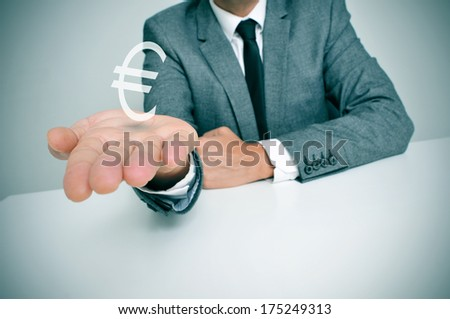 a businessman sitting in a desk showing a euro sign in his hand - stock photo