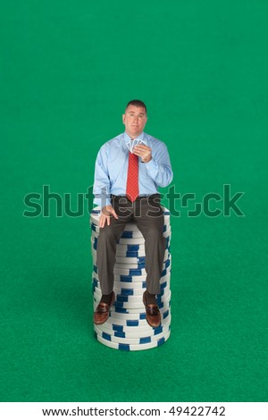 A businessman sitting on a stack of poker chips with a five card hand dealing with risk, success, chance or strategy. - stock photo