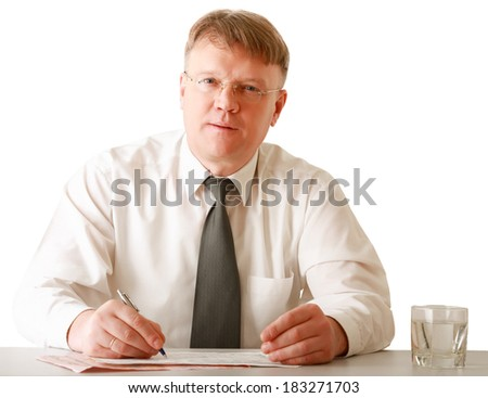 A businessman sitting on the desk and writing, isolated on white background - stock photo