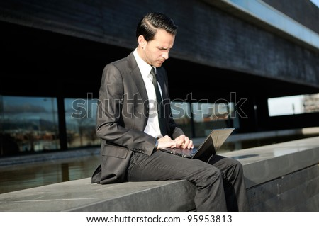 A businessman sitting on the floor with a laptop computer - stock photo