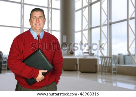 A businessman stands with his leather folder in a large lobby waiting for a meeting - stock photo