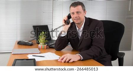 A businessman talking on landline phone at office - stock photo
