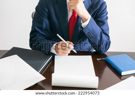 A businessman thinking before writing - stock photo