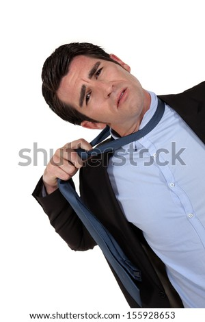 A businessman untying his tie. - stock photo