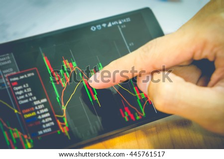 A businessman using a mobile device to check market graph. vintage filter effect. focus on screen. - stock photo