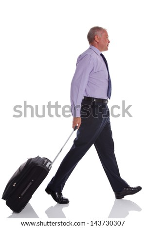 A businessman walking along pulling a suitcase, isolated on white background. - stock photo