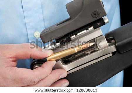 A businessman wearing a dress shirt loads an assault rifle with a single 223 bullet - stock photo