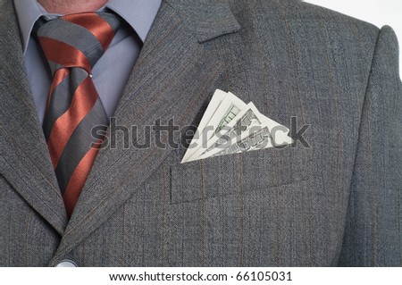 A businessman wearing a suit and tie with cash sticking out of his pocket. - stock photo
