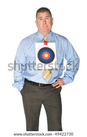 A businessman with a bulls eye target taped to his dress shirt. - stock photo