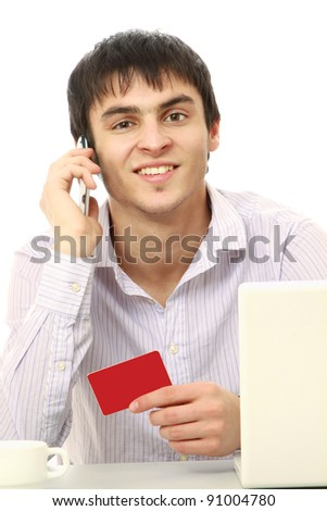 A businessman with a credit card, laptop sitting at the desk and talking on phone , isolated on white background - stock photo