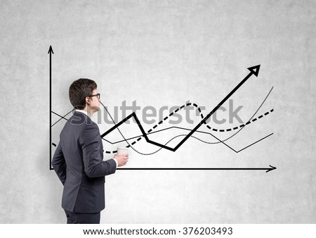 A businessman with a paper cup looking at graphs drawn on a concrete wall. Side view. Concrete background. Concept of defining a trend. - stock photo