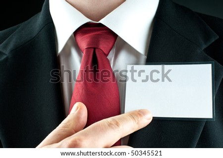 A businessman with a tie points on a blank name-tag - stock photo