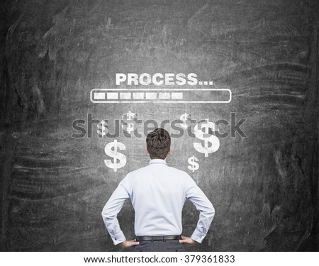 A businessman with hands on hips thinking about earning money, the word 'processing' and dollar signs painted over him. Back view. Black background. Concept of earning money - stock photo