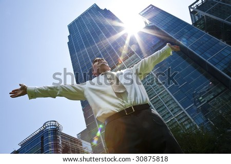 A businessman with his arms out stretched 'messiah like' in a modern city environment with the sun bursting over glass fronted office buildings behind him - stock photo