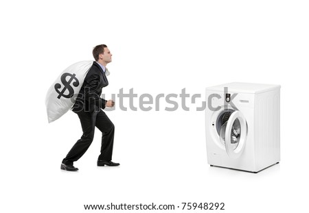 A businessman with money bag on his back going towards a washing machine isolated on white background - stock photo
