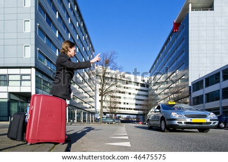 A businessman with several suitcases flagging a taxi - stock photo