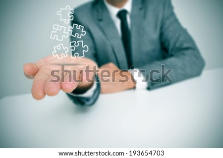 a businessman with some jigsaw puzzle pieces in his hand - stock photo