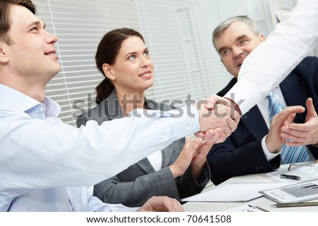 A businessmen shaking hands and his team applauding them - stock photo