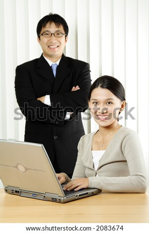 A businesswoman and a businessman in an office - stock photo