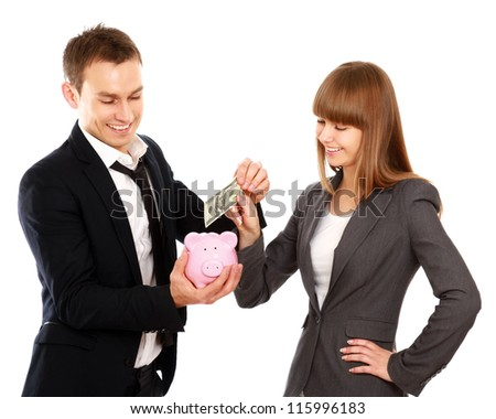 A businesswoman and man putting a coin into a piggy bank isolated on white background - stock photo