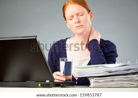 A businesswoman experiencing physical discomfort - a pain in her neck due to stress or too much work. - stock photo